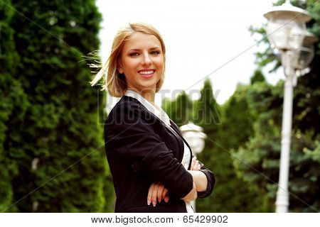 Portrait of a smiling attractive woman with arms folded in park