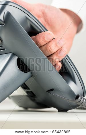 Hand Picking Up The Receiver Of A Black Telephone