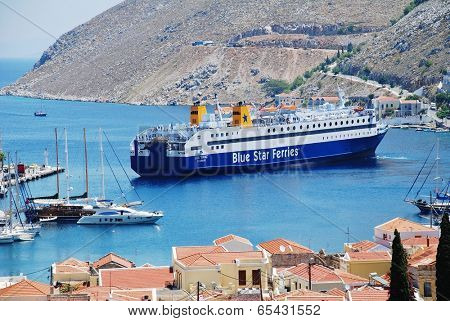 SYMI, GREECE - JUNE 18, 2011: Blue Star Ferries ship Diagoras docks at Yialos harbour on the Greek island of Symi. The 141mtr ship was built in 1990.