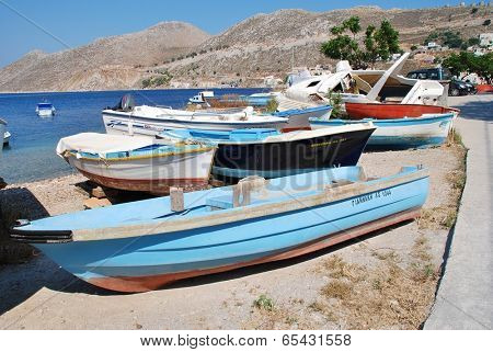 SYMI, GREECE - JUNE 18, 2011: Small boats beached at the Harani boatyard at Yialos on the Greek island of Symi. The island is a popular destination for day trippers from Rhodes and nearby Turkey.