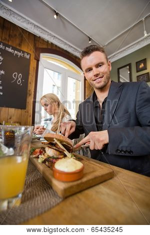Portrait of young businessman having food with colleague in coffeeshop