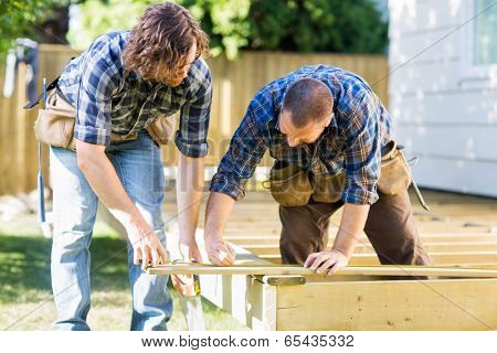 Mid adult carpenter marking wood while building deck