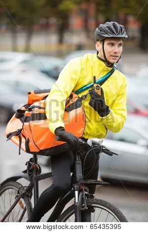 Young male cyclist with courier delivery bag using walkie-talkie on street