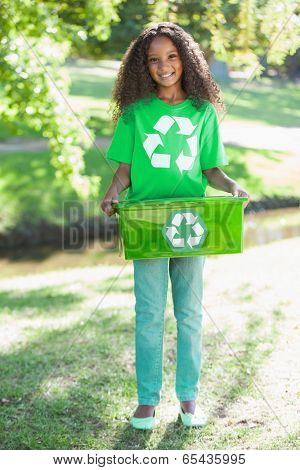 on a sunny Young environmental activist smiling at the camera holding box day