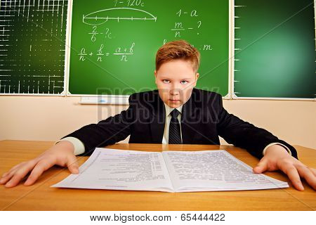 Serious schoolboy in uniform sitting at his desk at a classroom.