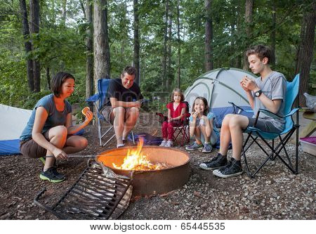 family of five people camping and having fun cooking over fire