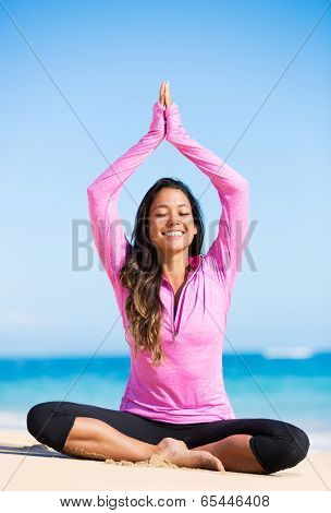 Happy relaxed young woman practicing yoga outdoors at the beach. Healthy natural lifestyle.