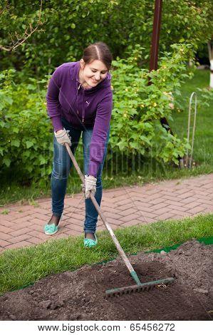 Beautiful Woman Working With Rake On Garden Bed