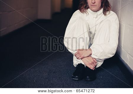 Woman In Boiler Suit Sitting In Corridor