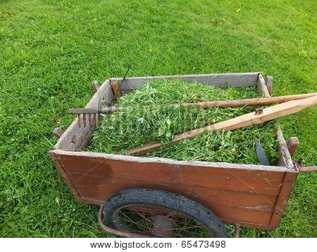 Old Truck With Mown Grass With A Scythe, Rake And Whetstone