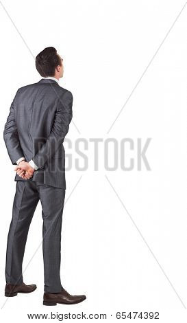 Businessman standing with hands behind back on white background