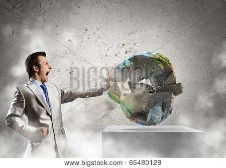 Young determined businessman crashing Earth planet with punch. Elements of this image are furnished by NASA