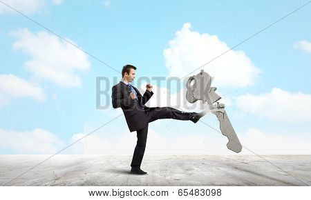 Angry businessman crashing stone key with punch