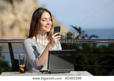 Happy Woman In A Restaurant With A Computer And On The Phone
