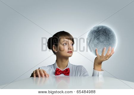 Young woman holding balloon colored like moon planet