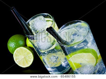 Two Glasses With Cocktail And Ice With Lime Slice On Black Table
