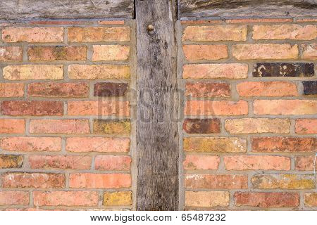 Old brick wall facade with wooden post
