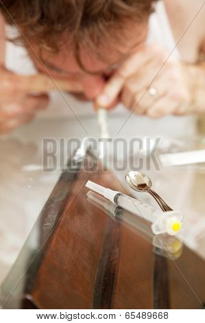 Man abusing cocaine or other powdered drug.  Shallow depth of field with focus on syringe in the foreground.
