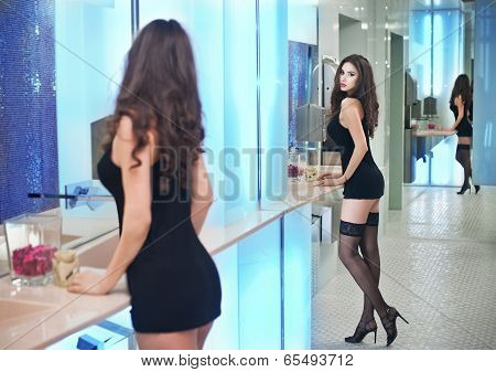 Sensual woman wearing a black short dress posing in a modern scenery. Beautiful and sexy brunette