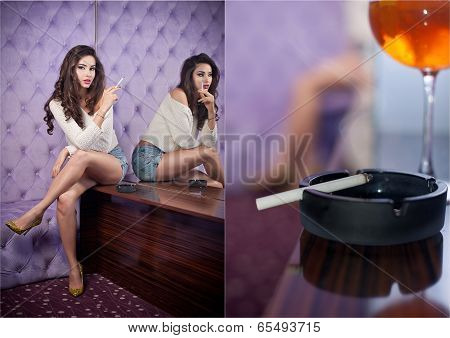 Beautiful brunette girl in denim shorts and white blouse posing on lilac textured background smoking