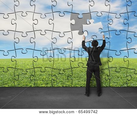 Businessman Assembling Last Missing Puzzle On Wall