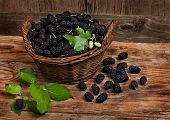 foto of mulberry  - basket with black mulberries on wooden background - JPG