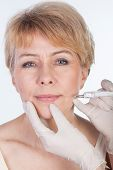 stock photo of latex woman  - Middle aged woman receiving a botox injection in her lips - JPG