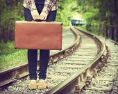 stock photo of passenger train  - young woman with old suitcase on railway departing train on background retro stylized - JPG