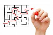 stock photo of overcoming obstacles  - Hand drawing an red arrow going through a maze - JPG