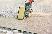 stock photo of grout  - Worker with machine grouting compound street paved with bricks - JPG