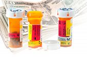 foto of twenty dollars  - Medicine bottles and a stack of twenty dollar bills with white vignette - JPG