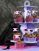 pic of three tier  - Graduation day pink and purple party cupcakes with chocolate frosting on polka dot three tier stand and large graduation cap - JPG