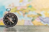 foto of cartographer  - compass on the table against the background of a tourist map - JPG