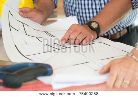 Close-up Of Two People Discussing Plan On Blueprint