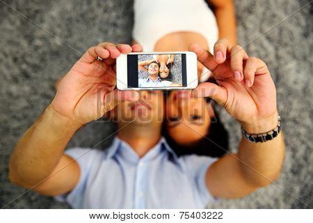 Couple lying on the carpet and making selfie photo on smartphone. Focus on smartphone