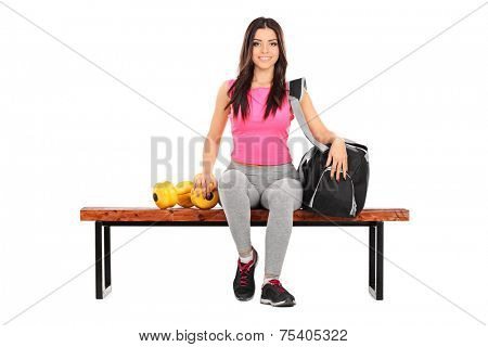 Female athlete sitting on a bench with her training equipment isolated on white background