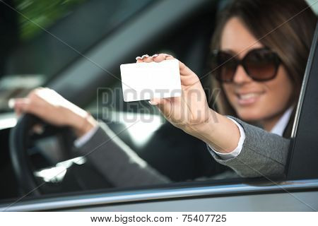 Young Woman Driving And Holding Business Card