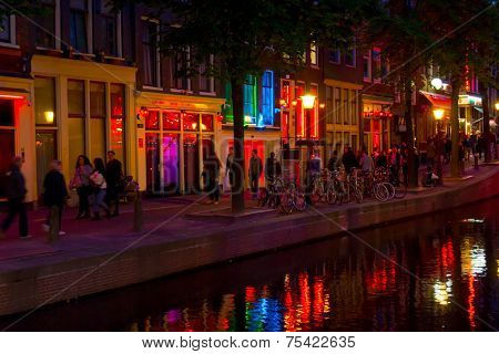 AMSTERDAM, NETHERLANDS - AUGUST 28: Tourists visit Red Light District at night on August 28, 2014 in Amsterdam, Netherlands. In this area there are prostitutes, sex shops and live sex shows