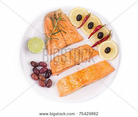 Fried salmon fillet with kalamata olives.