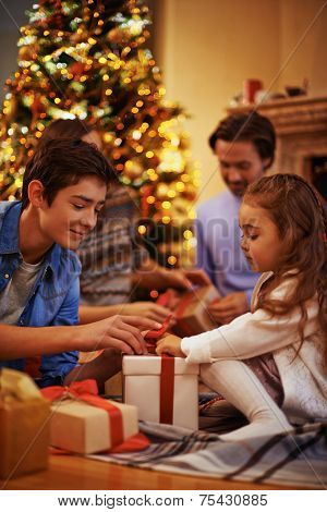 Youthful guy and his cute sister unpacking box with present on background of their parents