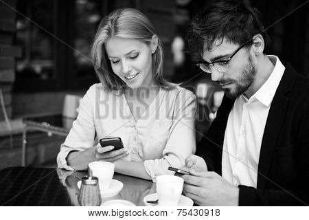 Modern man and woman using cellphones while sitting in cafe