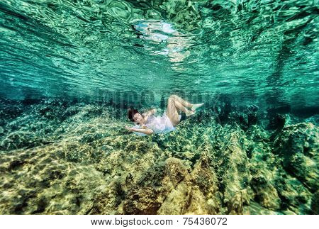 Dancing underwater, beautiful young female swimming in the sea near beautiful coral garden, active lifestyle, summer holidays and vacation concept