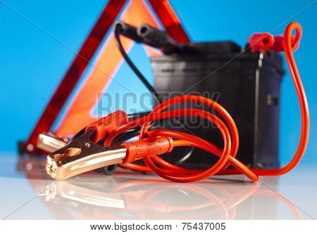 Car battery with two jumper cables clipped