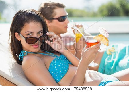 Side view of a young couple with drinks by swimming pool