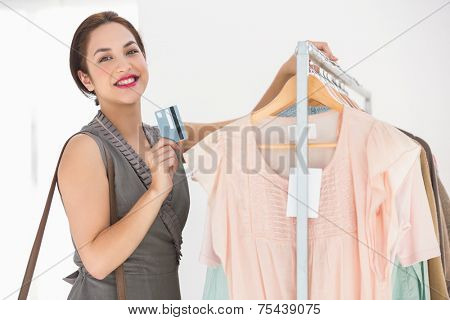 Pretty brunette leaning rail and holding credit card at clothes store