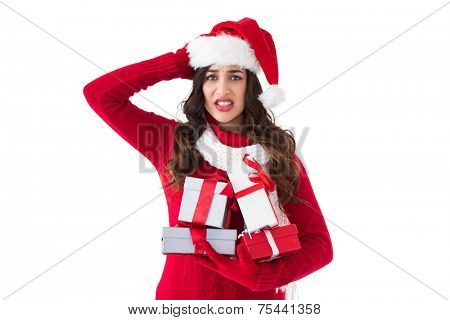 Stressed brunette in santa hat holding gifts on white background
