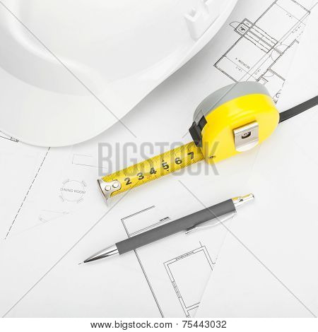 White Construction Helmet With Pencil And Measure Tape Above Blueprint