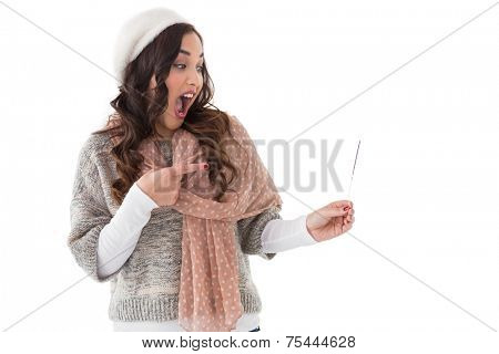 Astonished brunette in winter clothes on white background