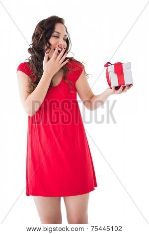 Astonished brunette holding a gift on white background