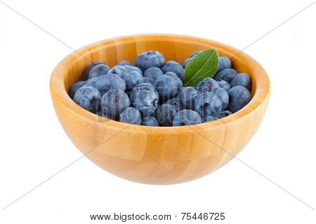 Wooden bowl with blueberry berries